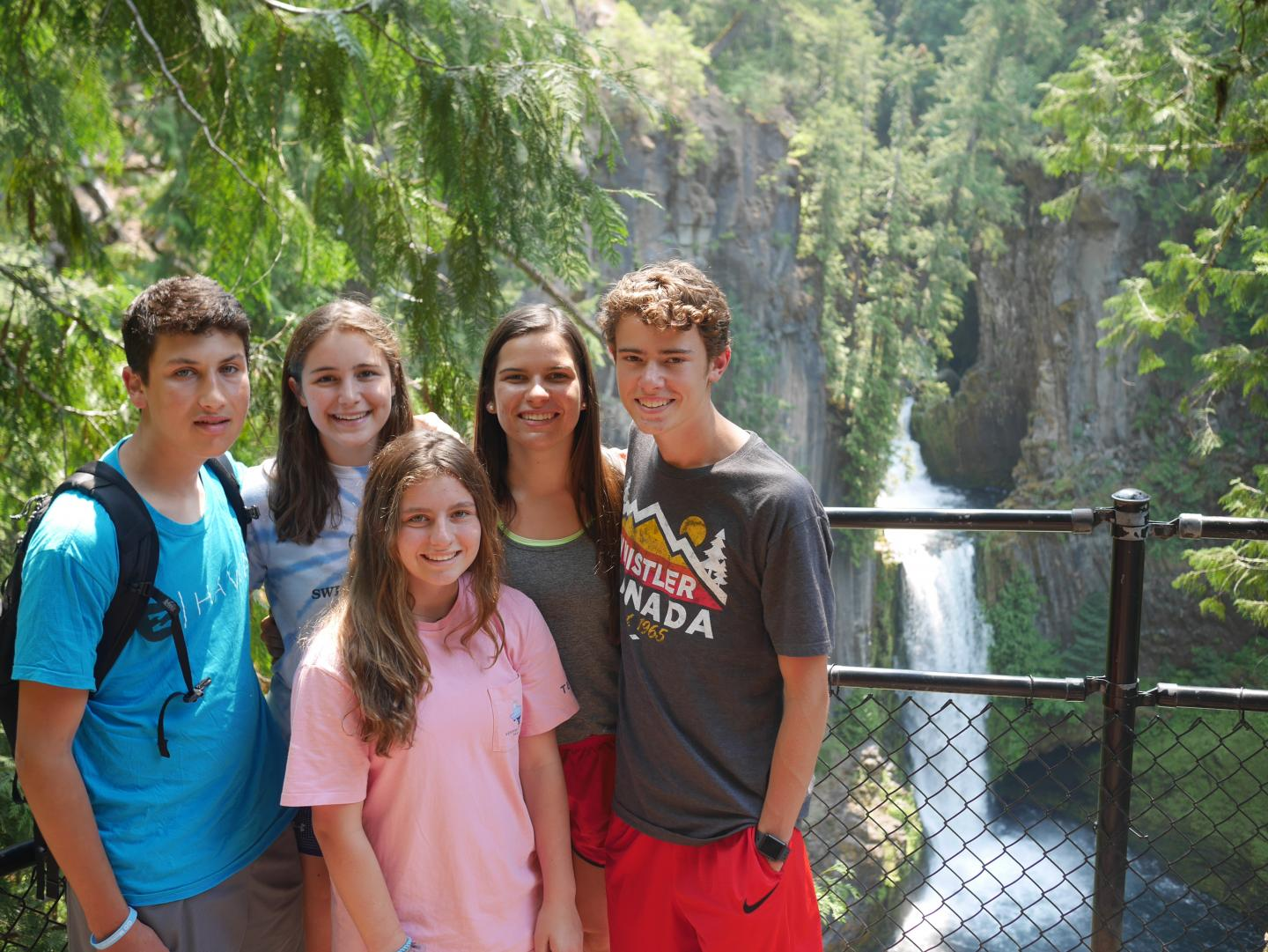A group of teens takes a photo at a waterfall during their summer travel program in North America.