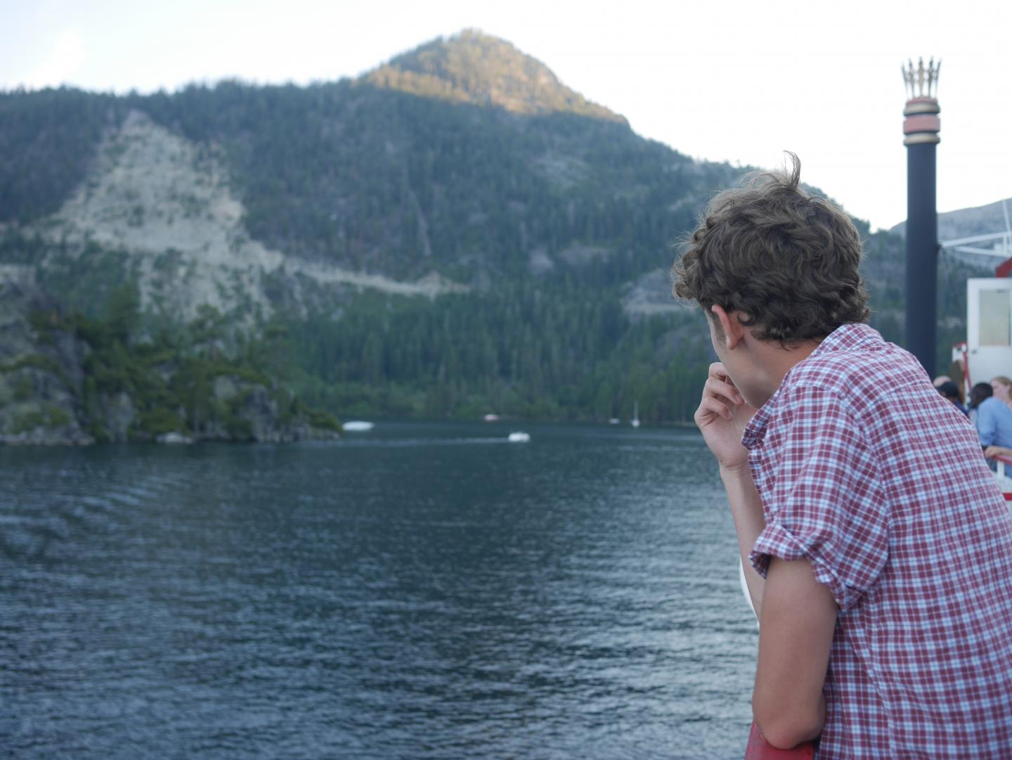 A teen gazes out at a lake during their summer adventure tour of North America.