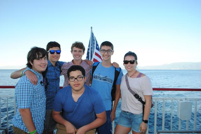 A group of friends rides a boat on a lake in North America during their summer teen travel tour.