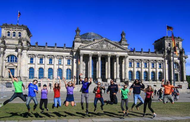 Happy teens jumping at Berlin Reichstag Building during summer teen travel program
