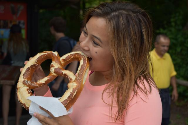 Teenage traveler enjoys authentic traditional local cuisine of pretzel in Bavaria Germany on summer youth travel program
