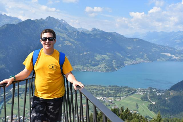 Teenage boy traveler at Harder Kulm Mountain Interlaken during summer youth adventure travel program