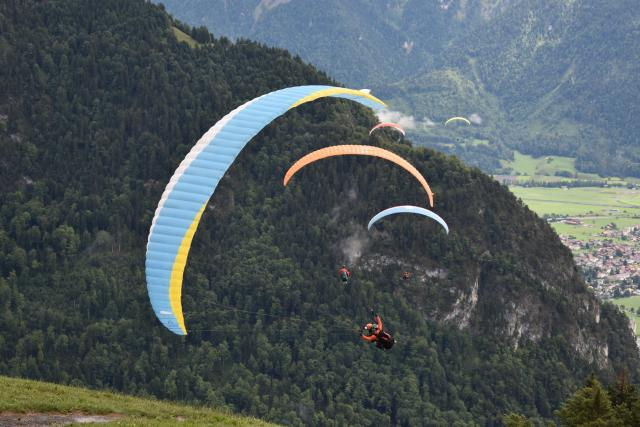 Teenage travelers paragliding in Swiss Alps during summer youth adventure travel program