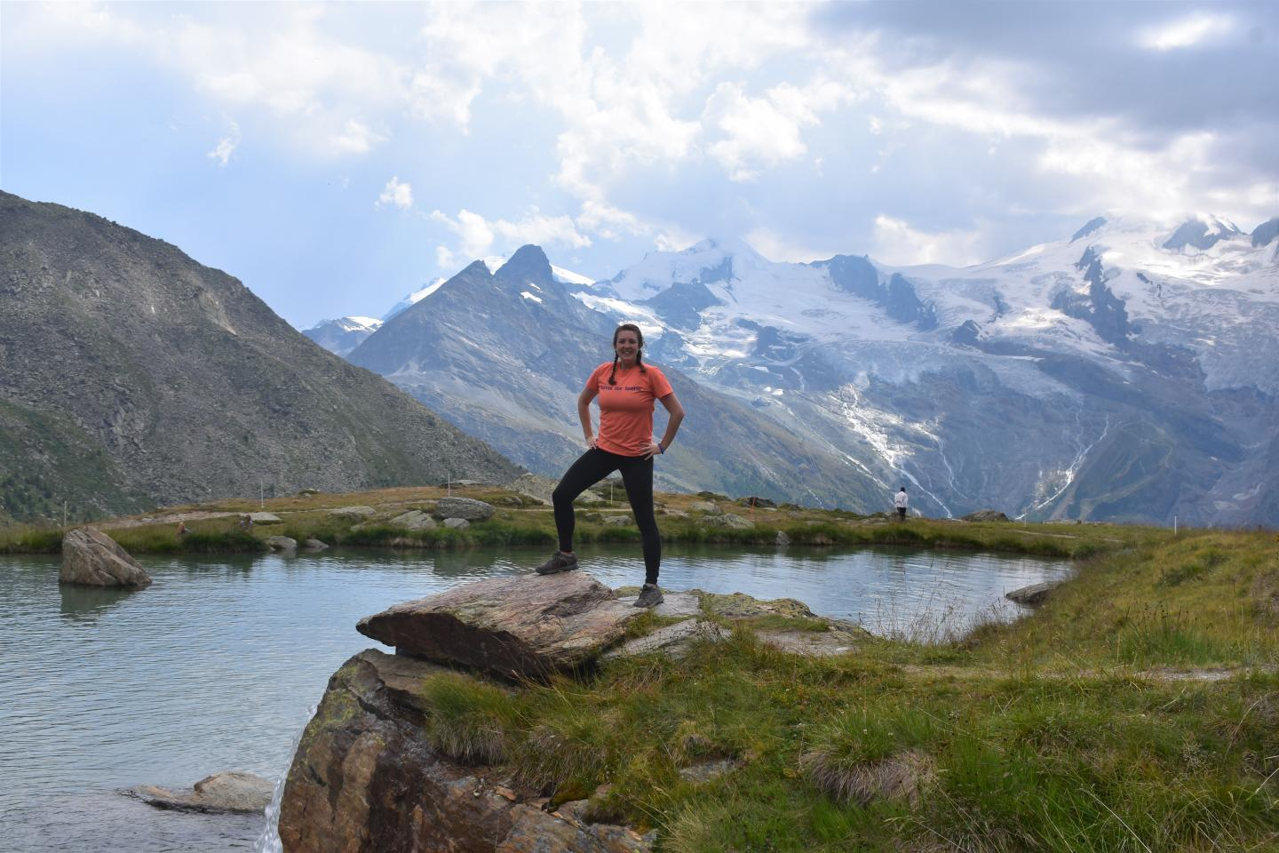 Teen traveler at Alpine lake in Swiss Alps during summer youth adventure travel program