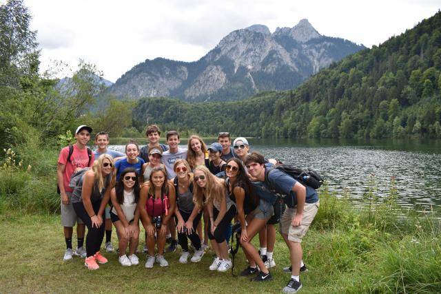 Group of teen travelers hiking in Swiss Alps with lake in background on summer youth travel program