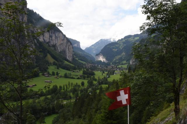 Swiss flag in mountain valley seen on summer teen youth adventure travel tour