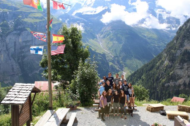 High school teen travelers hike in Swiss Alps during summer youth adventure travel program