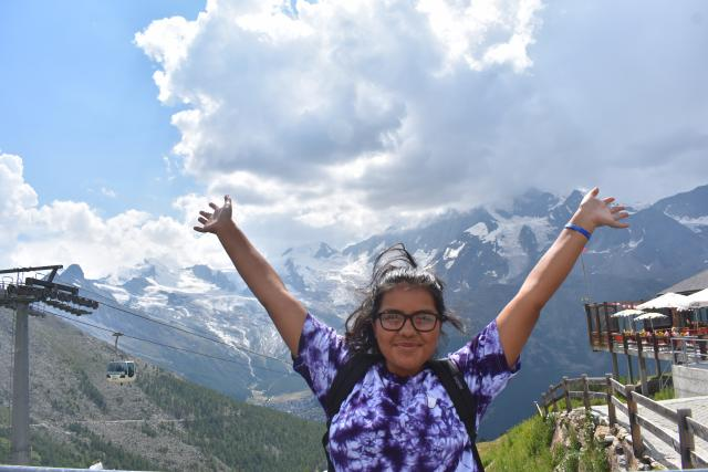 Happy teenage traveler in Swiss Alps on summer youth adventure travel program