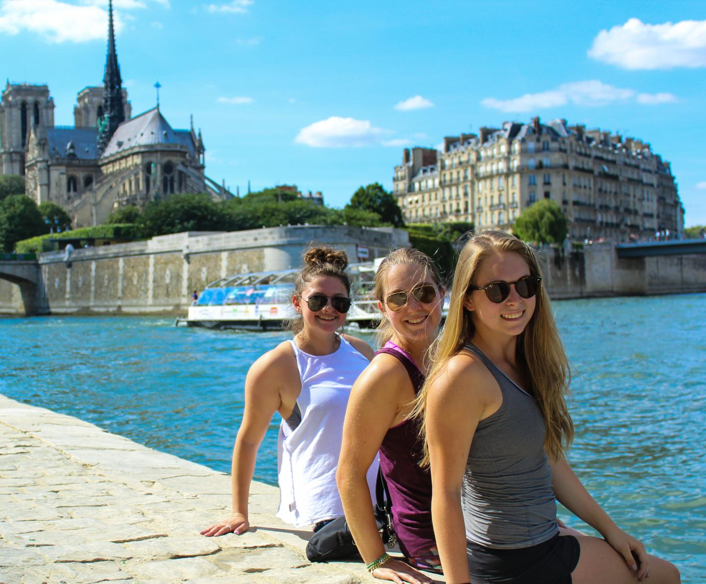 Teenage travelers relax at Notre Dame River Seine on Paris youth summer travel program