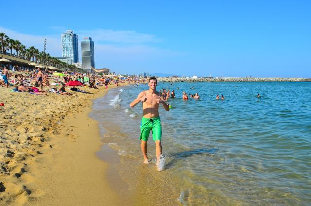 Teenage boy traveler on Barcelona beach during summer youth travel program
