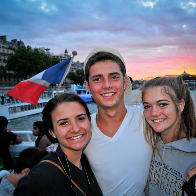 Teen travelers cruise down Seine at twilight on summer youth travel program