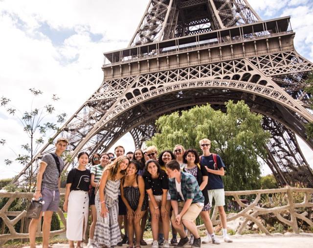 Teenage travelers visit Eiffel Tower on summer youth travel program in Paris