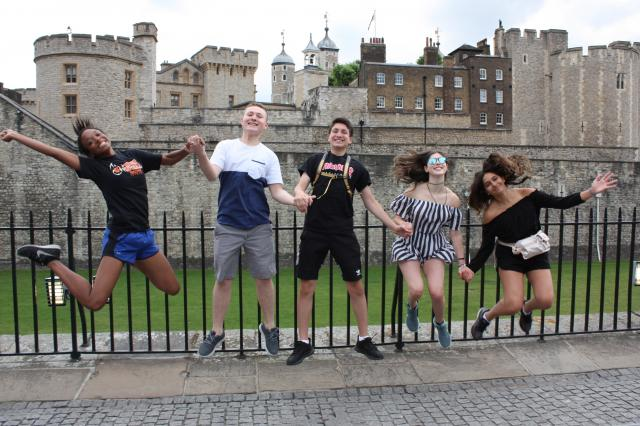 Happy teen travelers jump at Tower of London on summer travel program in England