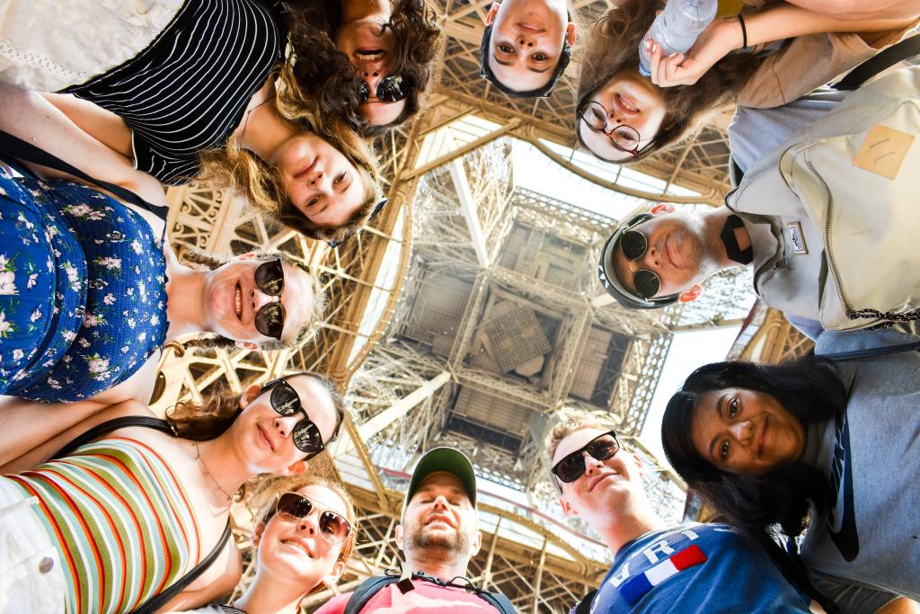 Teen travelers underneath Eiffel Tower during summer youth travel program in Paris