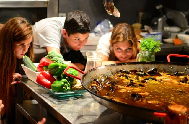 Teen travelers at paella cooking class during summer travel program to Spain