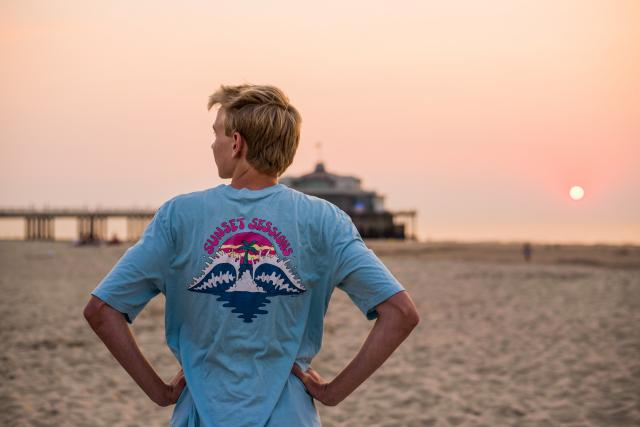 Teen traveler in Nice beach French Riviera watches sunset on summer youth travel program