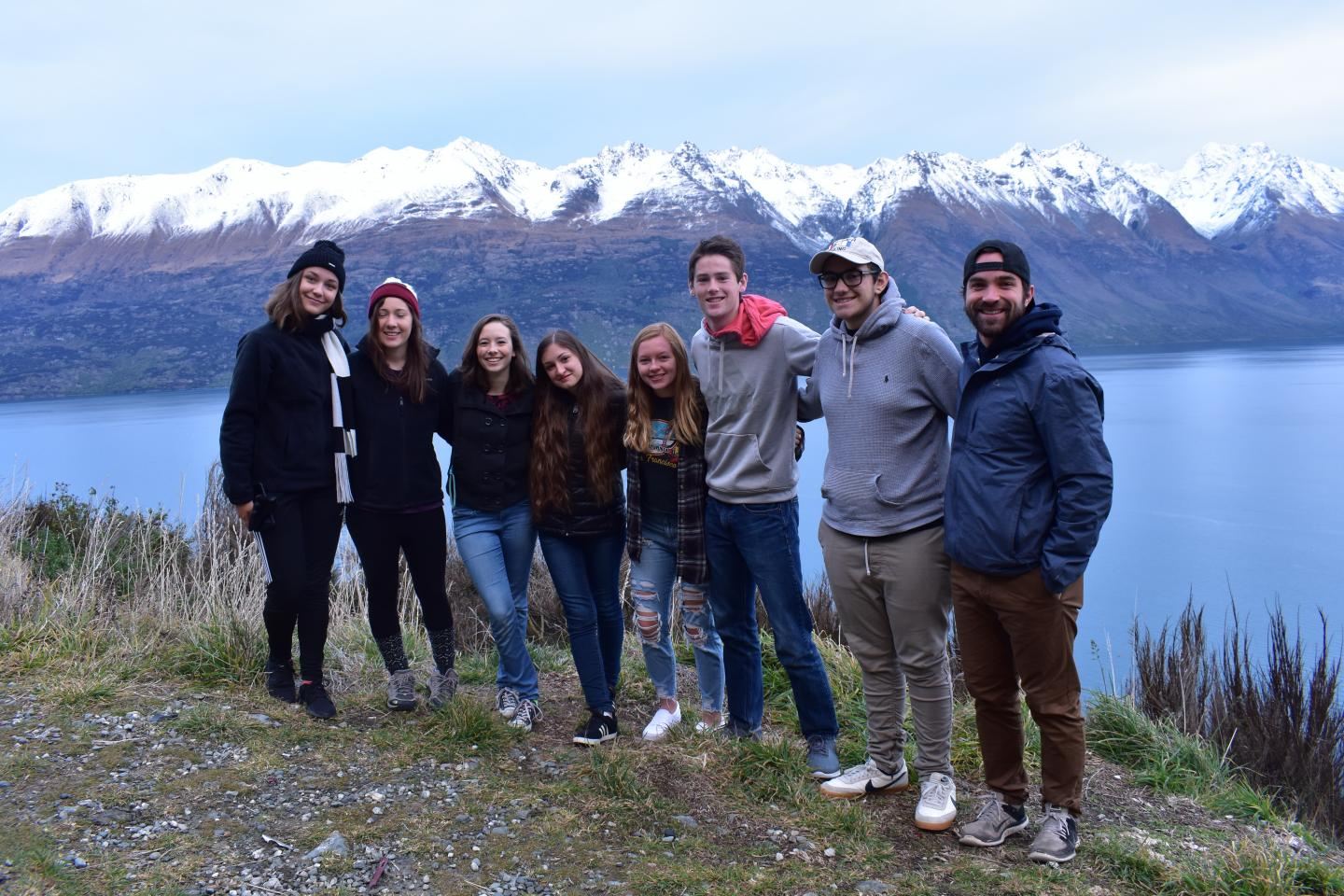 Teenage travelers visit lake and mountains during summer youth travel program in New Zealand