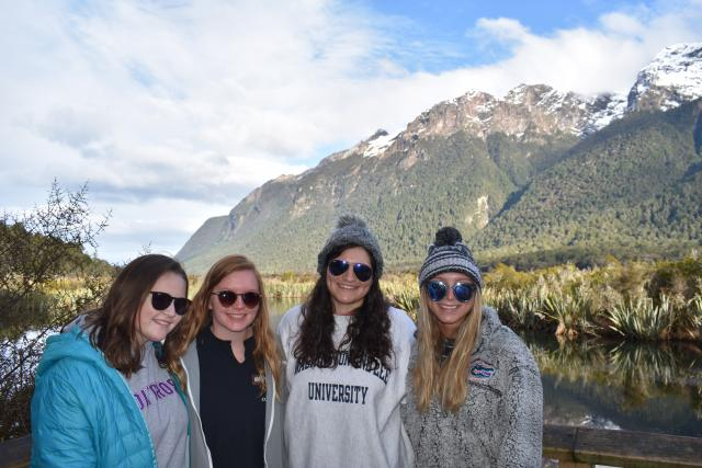 Happy teenage travelers admire scenery during summer youth travel program in New Zealand