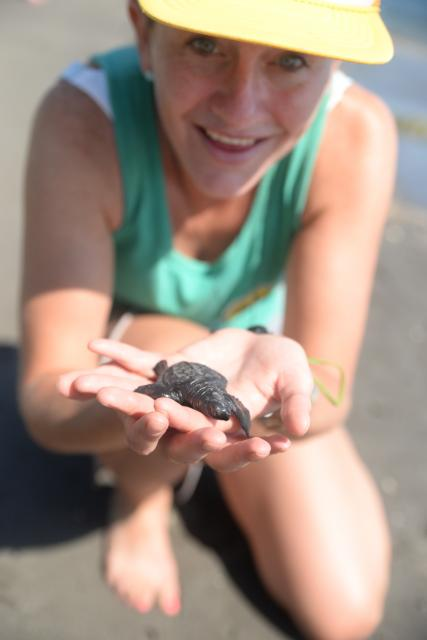 Girl holds baby sea turtle on teen service trip in Bali, Indonesia