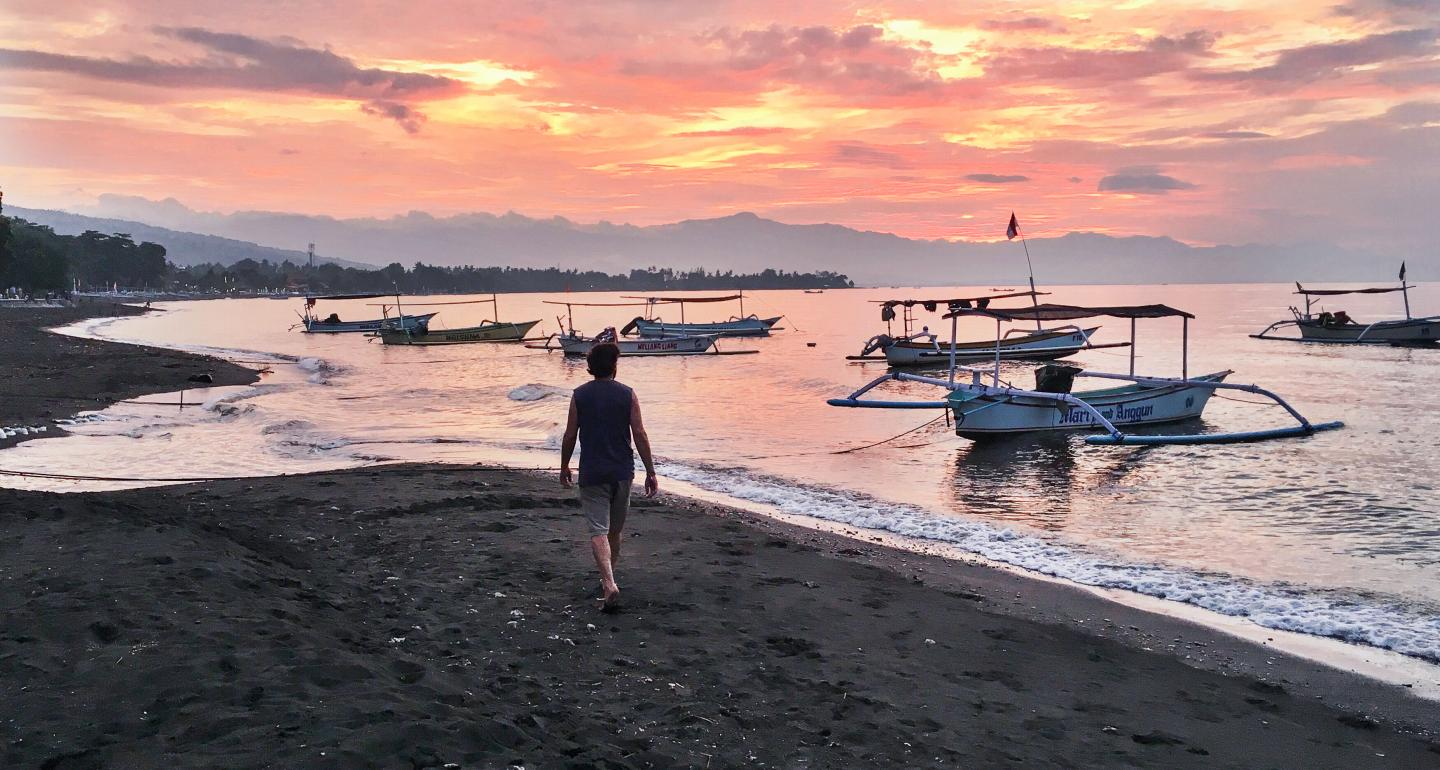 Teen walks along the beach at sunset in Bali, Indonesia