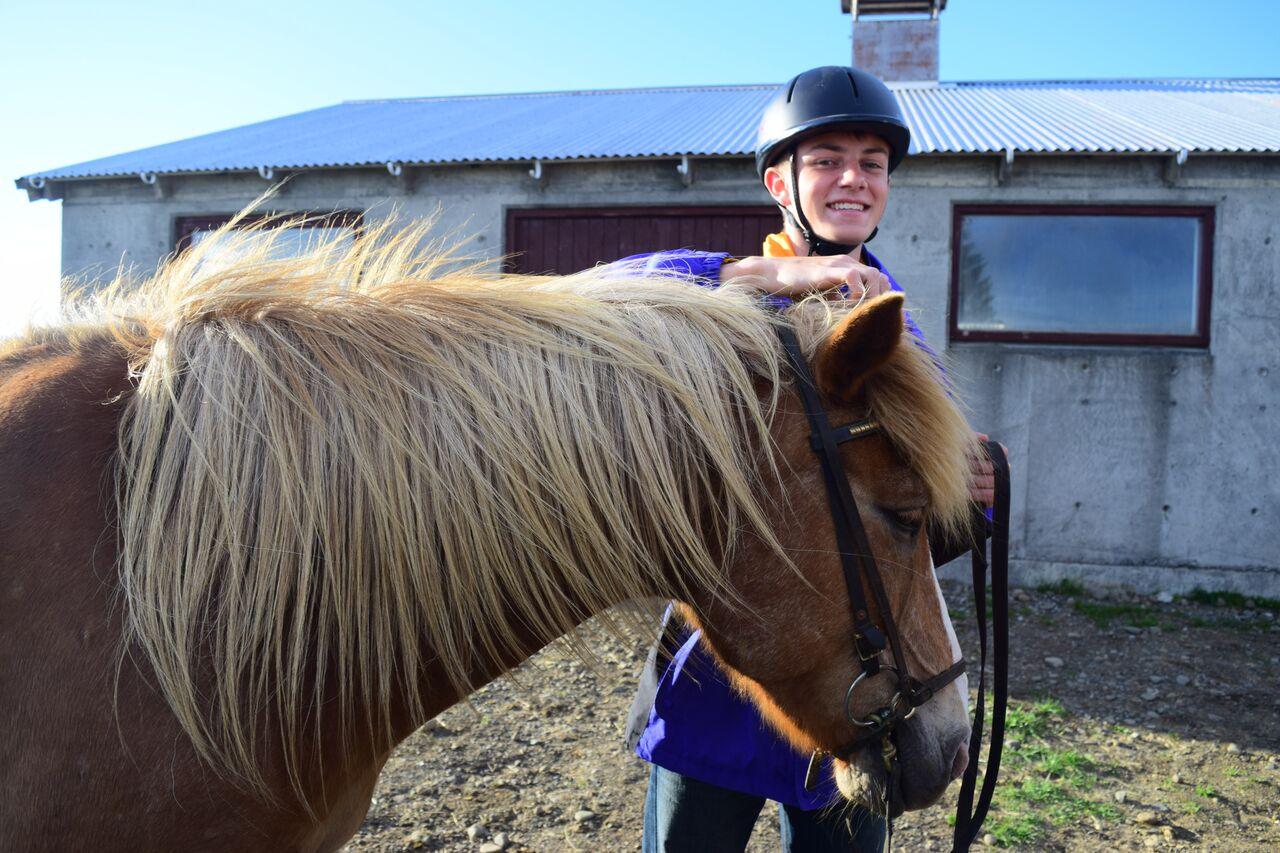 Teenage traveler riding Icelandic horse during summer adventure travel program