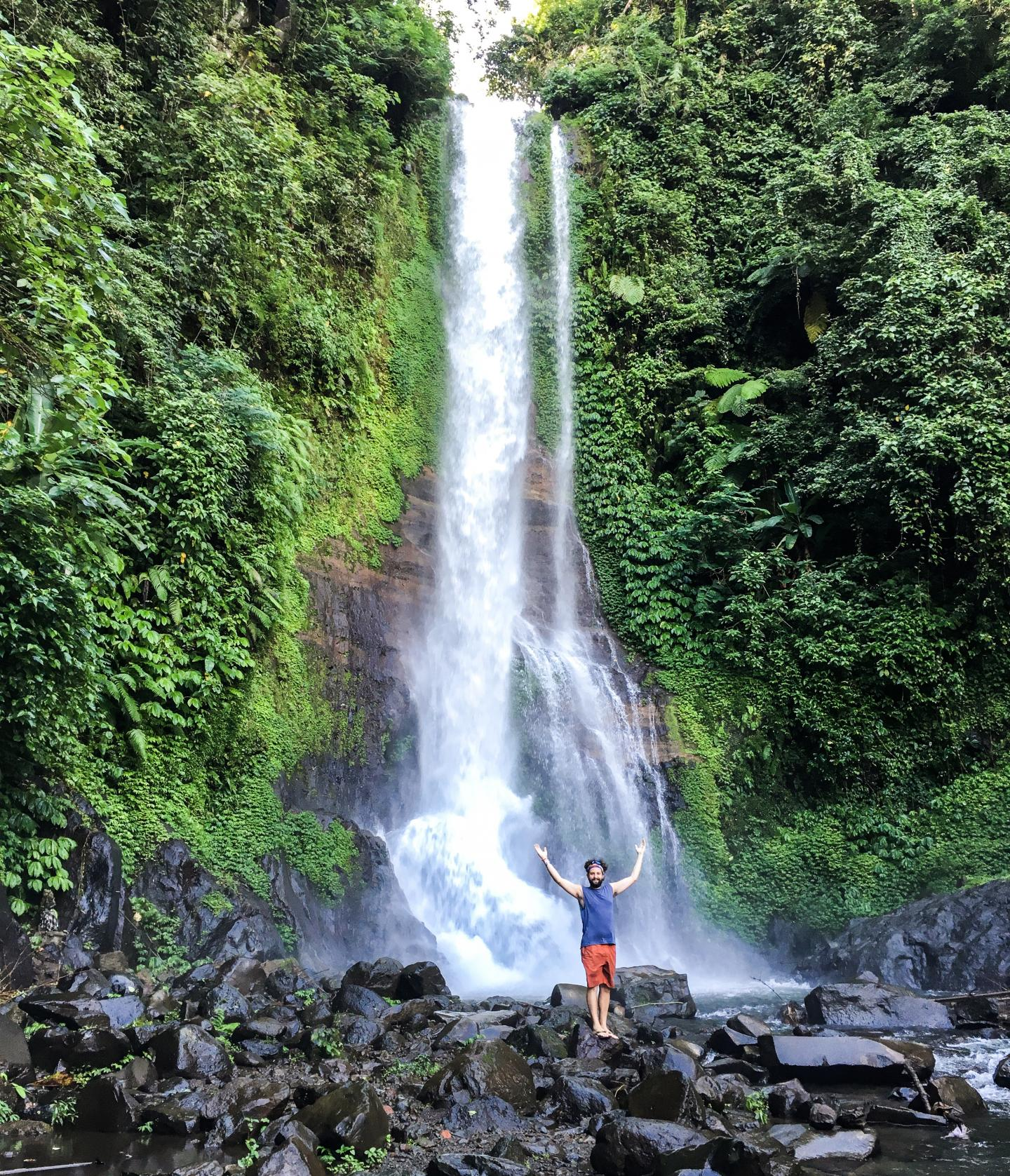 Teen in front of waterfall in Bali, Indonesia