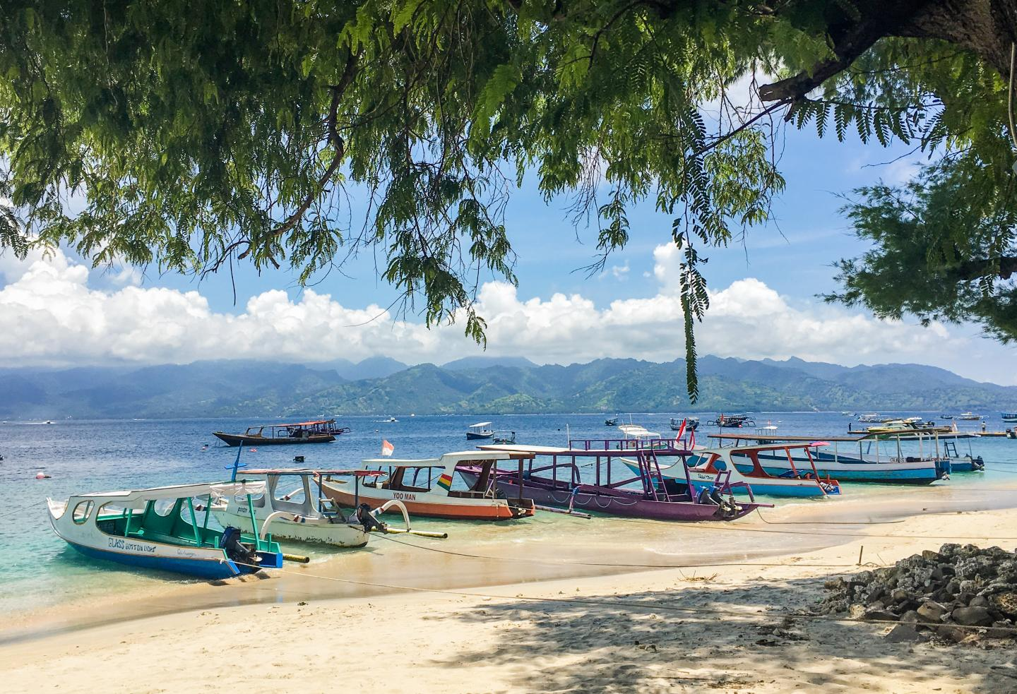 Boats line the shores of a beach in Bali, Indonesia