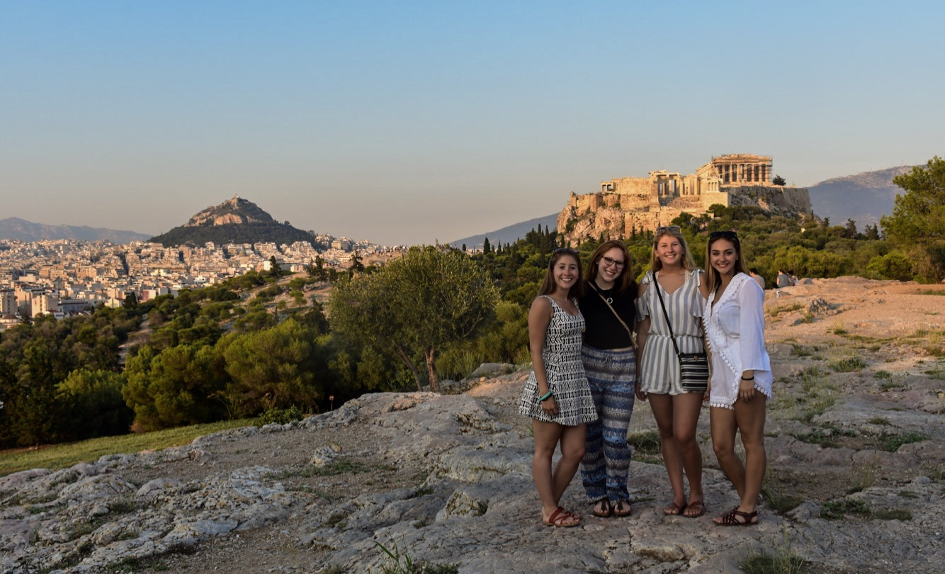 Teenage travelers visit Pnyx Hill and Greek Acropolis at sunset during summer youth travel program in Greece