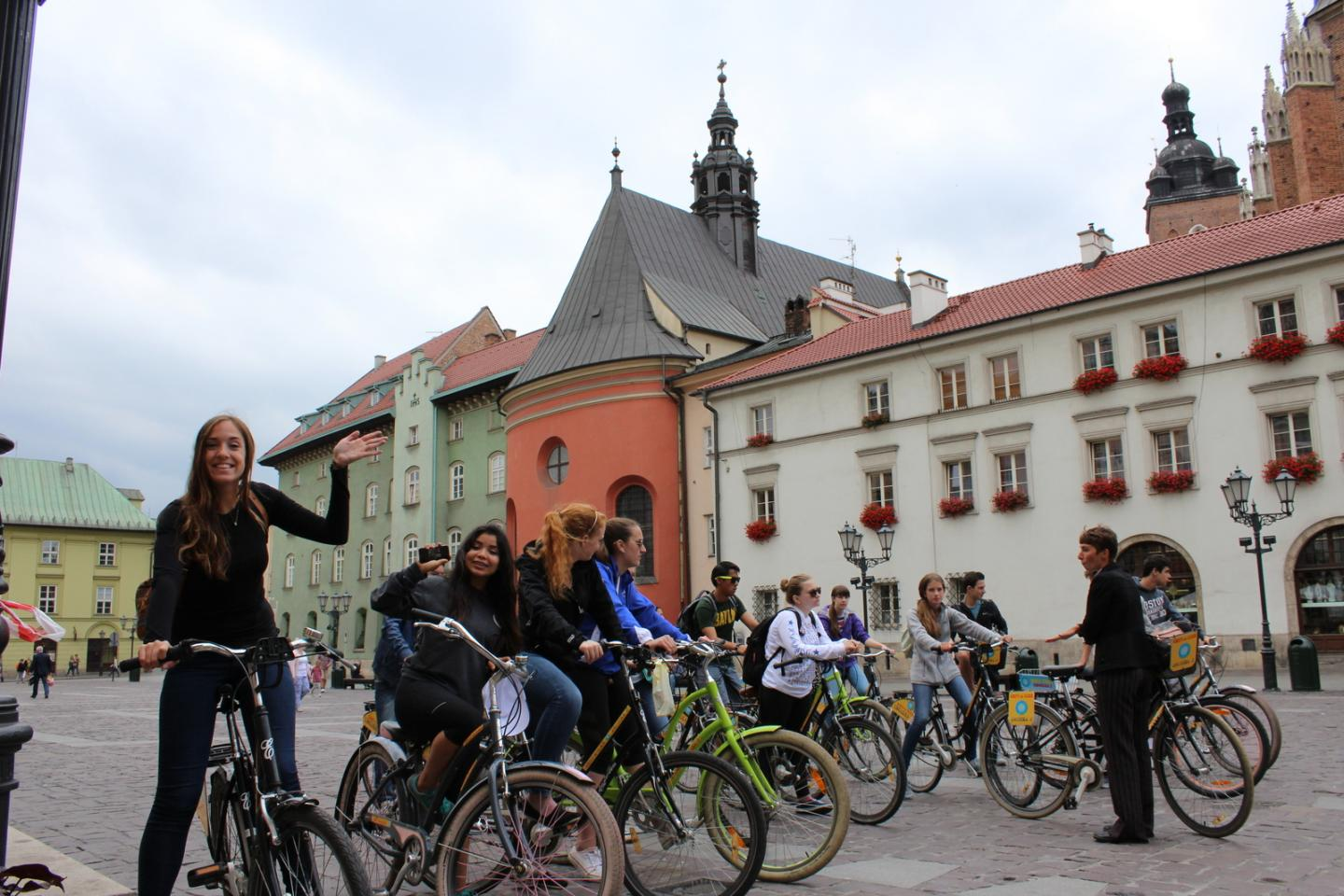 Happy teens biking through Krakow on summer teen travel program