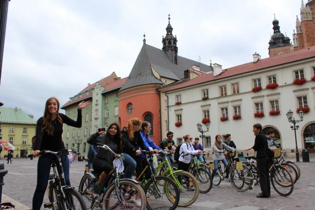 Happy teens biking through Krakow on summer teen travel program