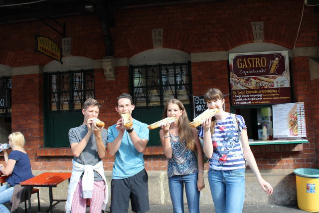 Teen travelers eat local authentic cuisine in Germany during summer youth travel program