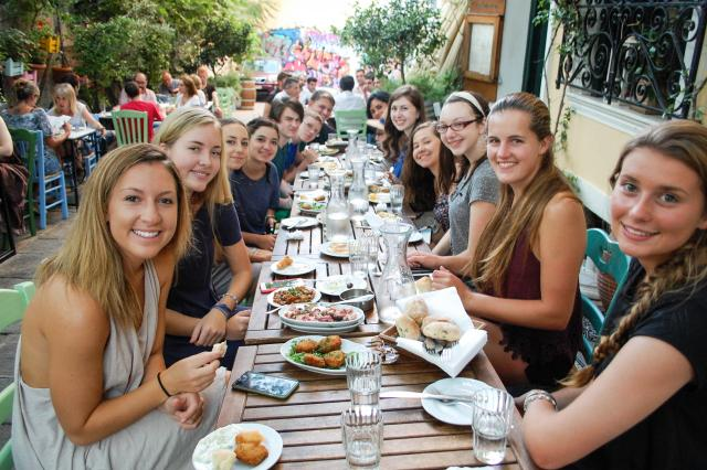 Teenage travelers enjoy delicious local specialties during summer youth travel program in Greece