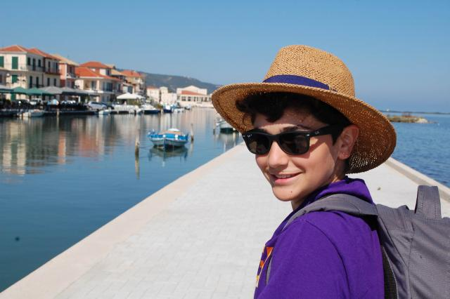 Teenage boy traveler explores Greek village and harbor during summer youth travel program in Greece