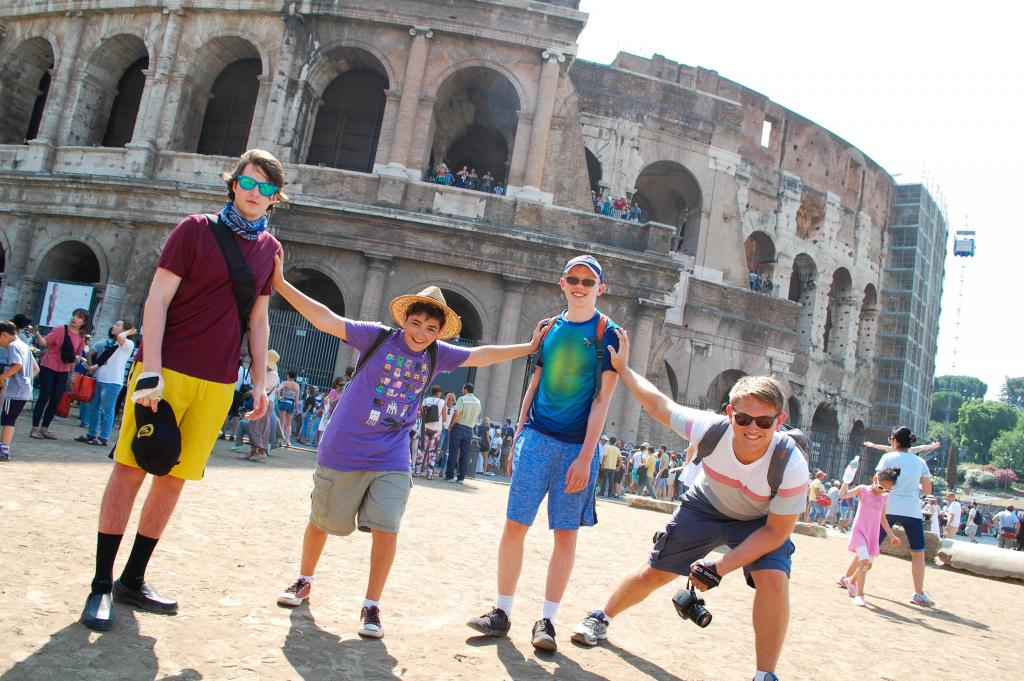Teenage travelers play outside Colosseum in Rome during summer youth travel program in Italy