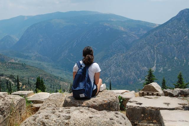 Teenage traveler admires breathtaking scenic views from atop Greek mountain during summer youth travel program in Greece