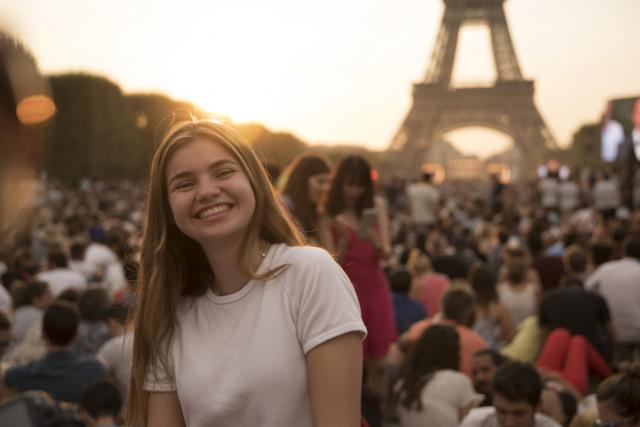 Teenage traveler with Eiffel Tower at sunset on summer photography program in Paris