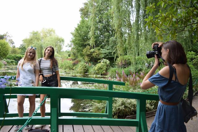 Teenage travelers taking pictures at Monet's Garden in Giverny during summer travel photography program