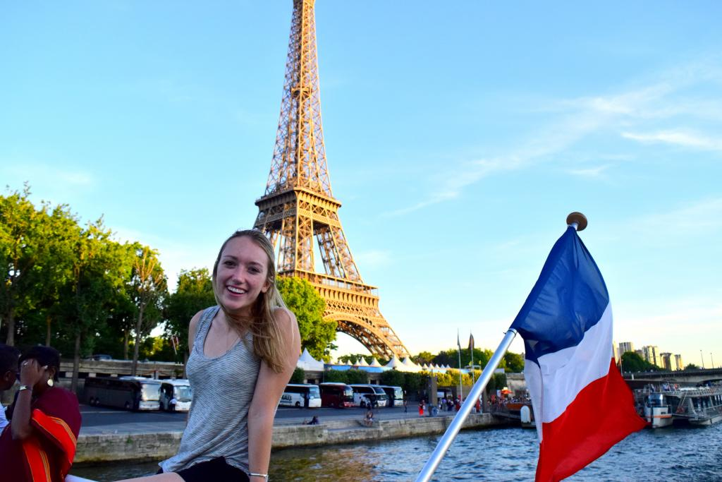 Teenage traveler on Seine river cruise with French flag and Eiffel Tower on summer travel photography program