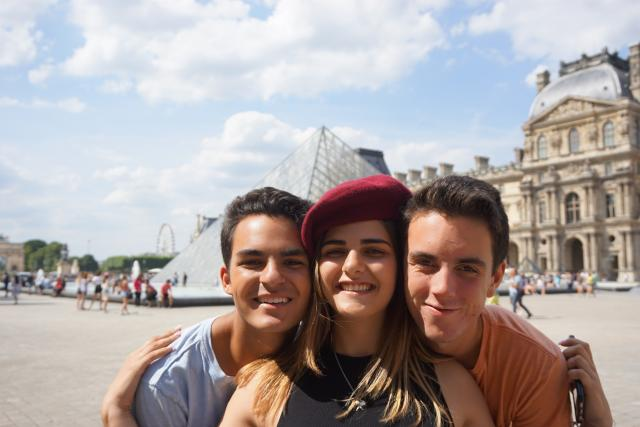 Teenage travelers at Louvre Museum in Paris during summer teen travel photography program