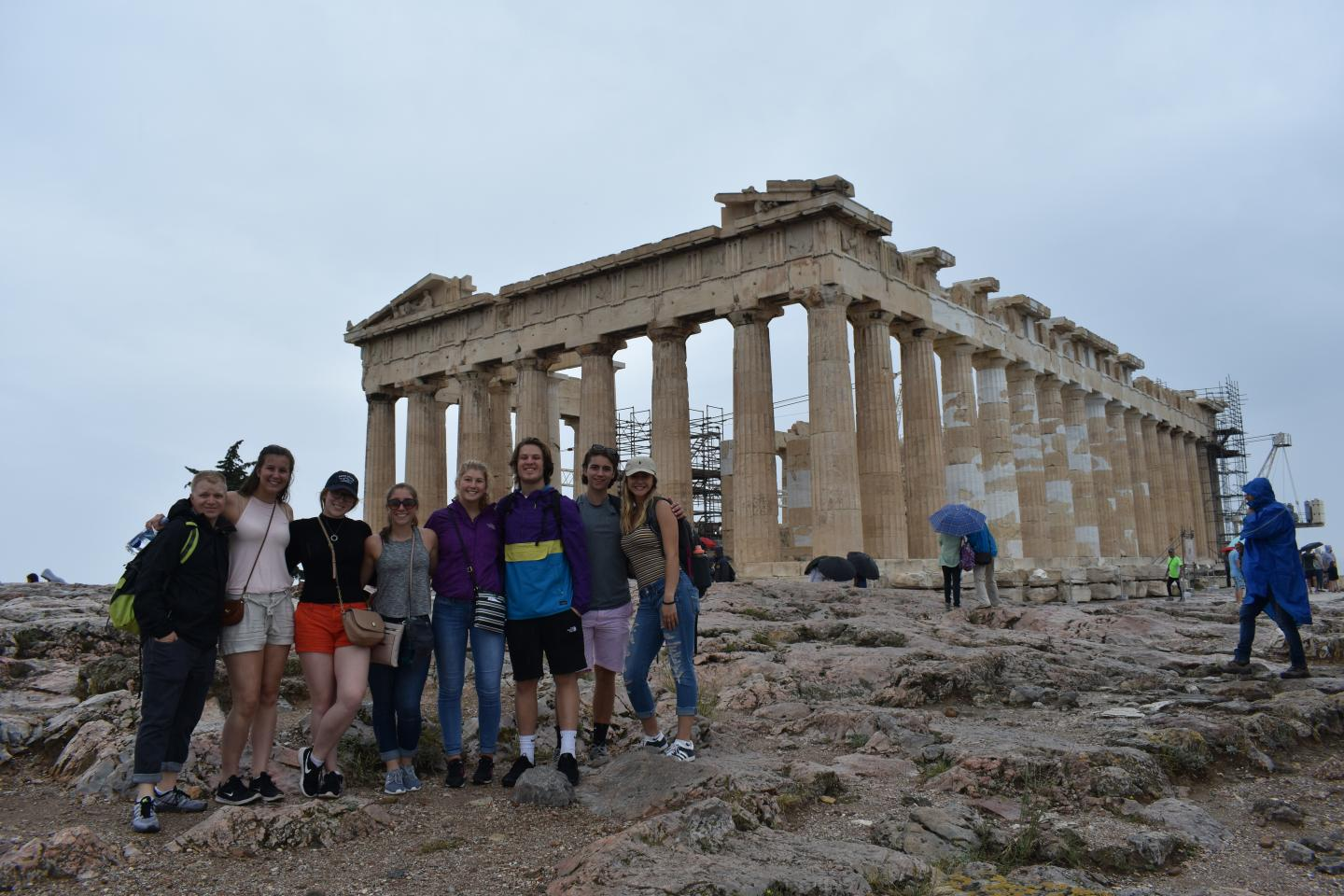Students smile in front of the Acropolis