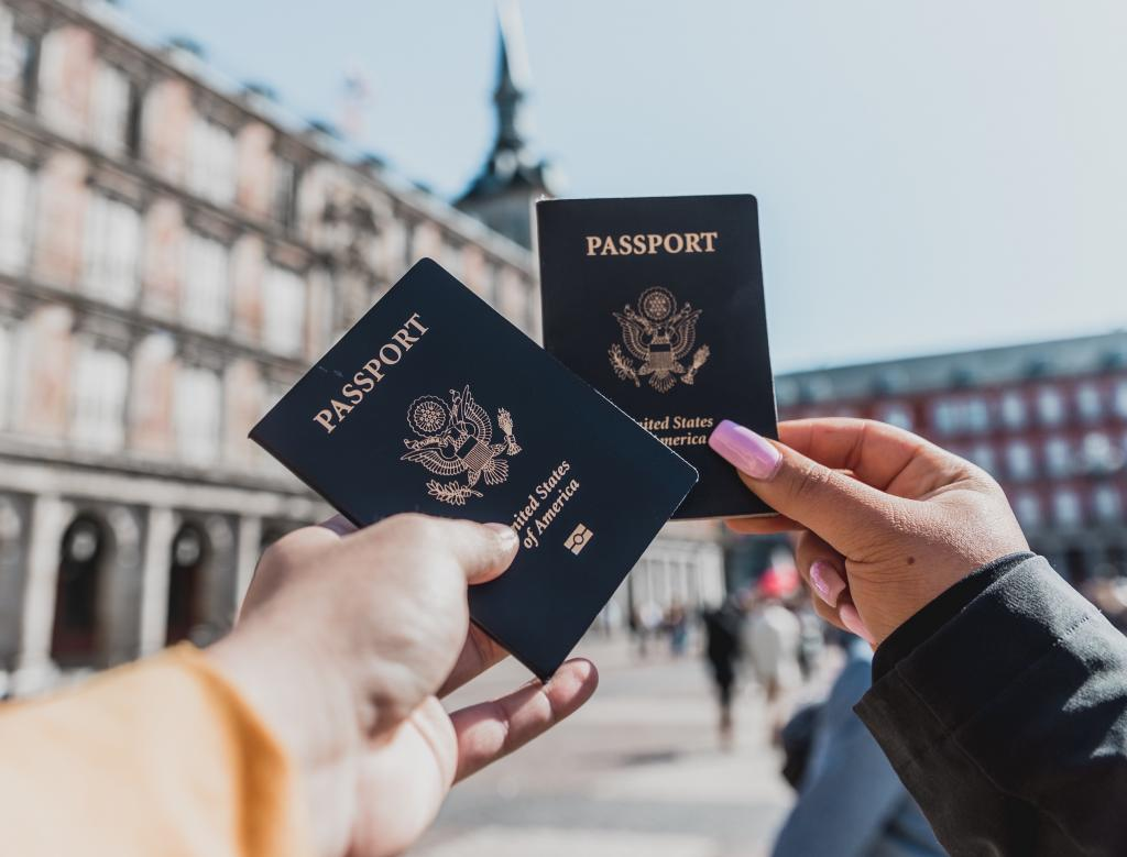 hands holding U.S. passports up in front of a European city scene