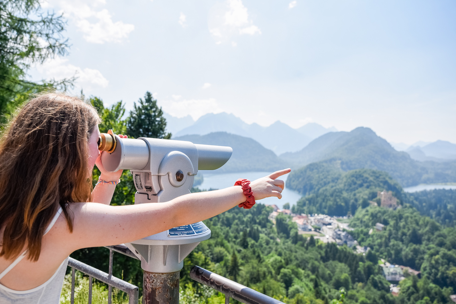teen girl pointing to landscape of mountains on a travel abroad trip