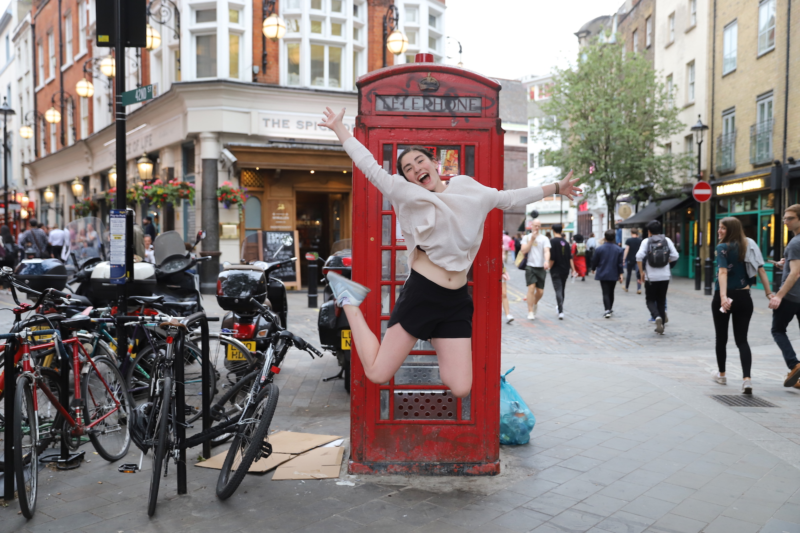Teen jumping in front of a London phone booth