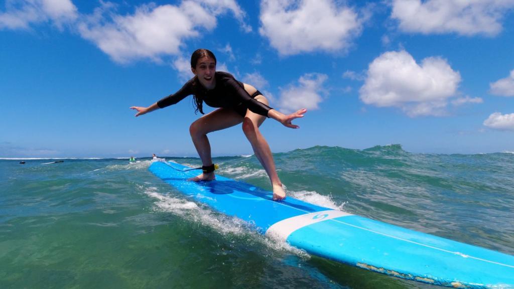 teen girl surfs in Hawaii
