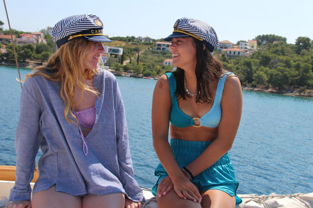 two teenage girl travelers on a boat in the mediterranean