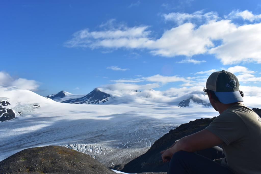 young male teen traveller looking at glacier in iceland