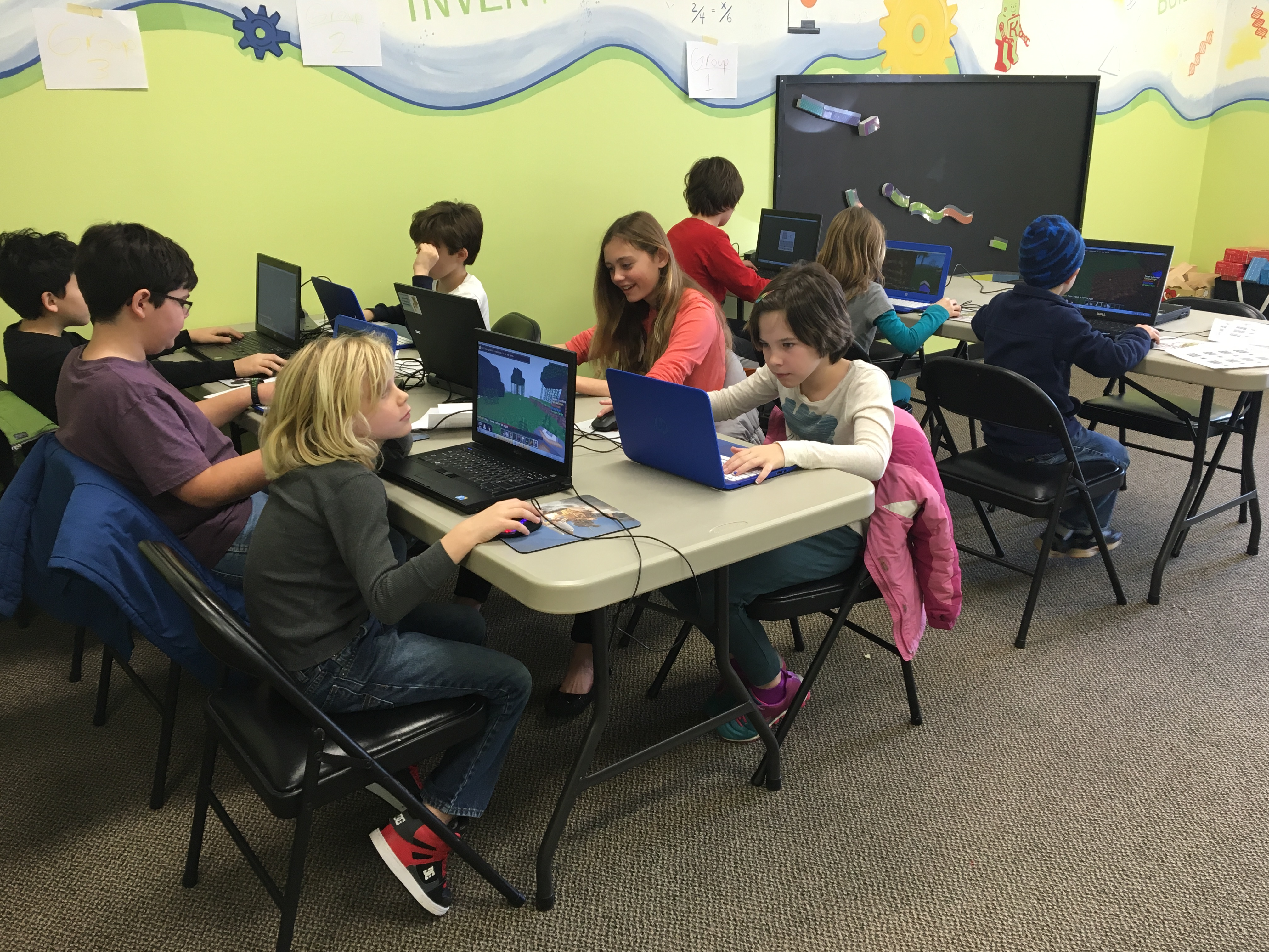 children at a summer stem camp playing on computers