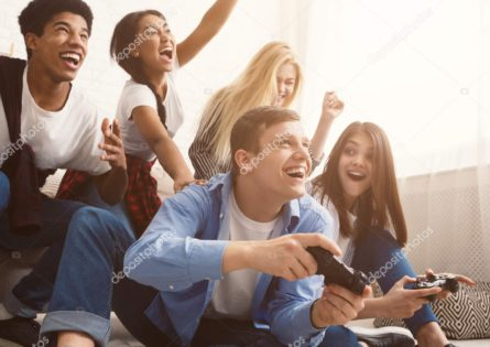 Teenagers having fun, playing video games online at home