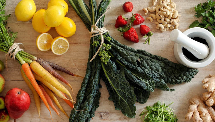 Colorful, Organic Vegetables and Fruit on a wood cutting board
