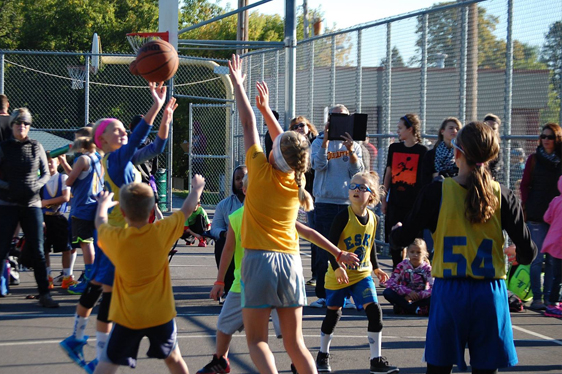Mixed gender rookie basketball team playing a game on an outdoor court